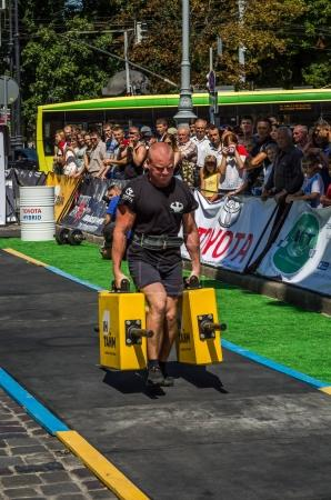 LVIV, UKRAINE - AUGUST 2017: A strong athlete a bodybuilder carries heavy iron suitcases, in exercise a farmer's walk, on the strongmen game in front of enthusiastic spectators