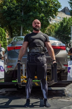 LVIV, UKRAINE - AUGUST 2017: Strong athlete the bodybuilder lifts the Toyota car in front of enthusiastic spectators at the Strongmen game