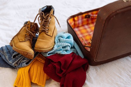 Photo for Woman clothes near old vintage suitcase. travel concept. preparing for winter trip - Royalty Free Image