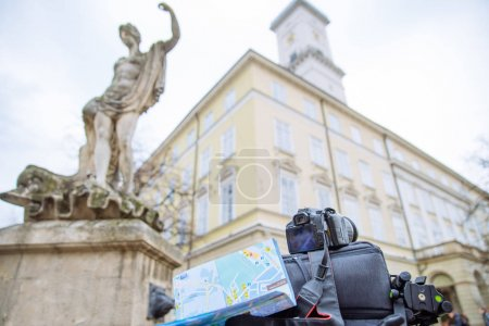 Photo for Travel concept. camera map and backpack with blurred european town on background - Royalty Free Image