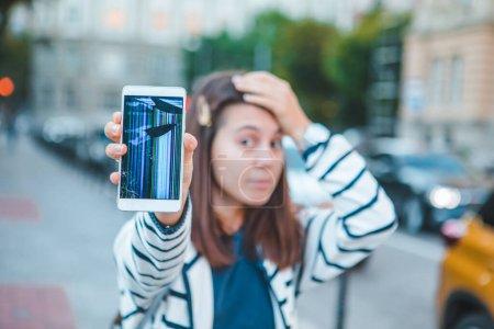 Photo pour La femme triste montrant fissuré écran mobile après goutte. service de réparation d'assurance - image libre de droit