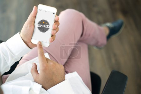 Photo for Male hands holding smartphone with text GARAGE SALE - Royalty Free Image