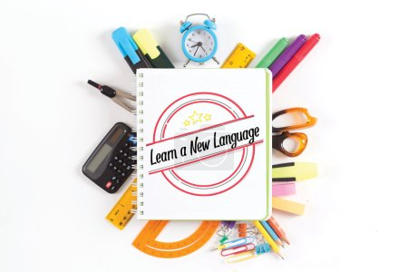Foto de Suministros de oficina y ordenador portátil con texto aprenden un nuevo idioma - Imagen libre de derechos