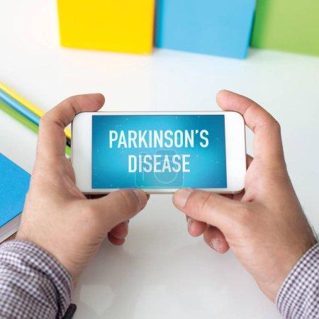 Photo pour Homme tenant le smartphone qui affiche la maladie de Parkinson - image libre de droit