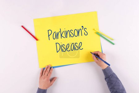 Photo pour Main qui écrit la maladie de Parkinson sur papier jaune - image libre de droit