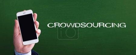 Photo pour Téléphone intelligent dans la main avant de blackboard et Crowdsourcing écrite - image libre de droit