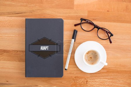 Notebook, cup ang glasses on desk.