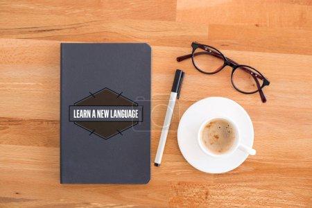 Foto de Notebook, taza gafas de ang en el escritorio. Aprender un nuevo concepto de lengua - Imagen libre de derechos