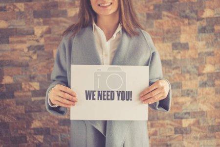 Photo pour Femme tenant en papier avec inscription nous avons besoin de vous - image libre de droit