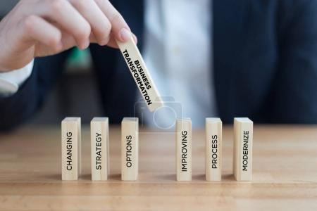 businessman playing with wooden blocks