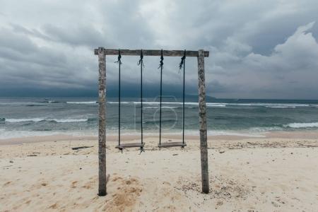 Foto de Columpios de madera en la orilla del mar, tiempo nublado - Imagen libre de derechos