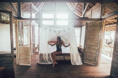 Photo pour Jeune femme au lit dans sa chambre à l'hôtel - image libre de droit