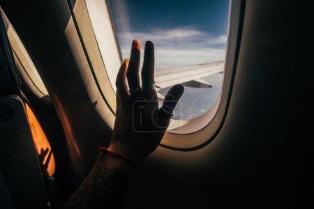 Woman hand on airplane window