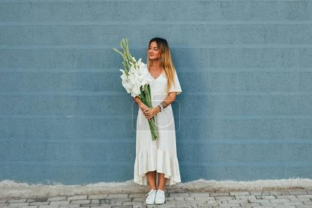 Foto de Hermosa joven con vestido blanco con ramo de flores - Imagen libre de derechos