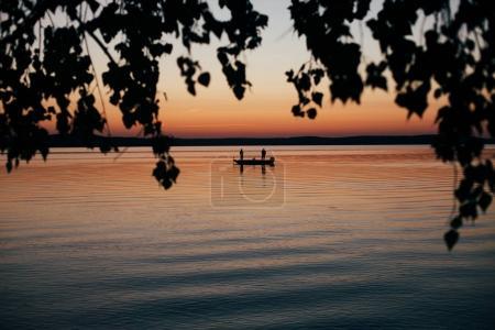 Photo pour Deux personnes, kayak sur le lac calm pendant le coucher du soleil avec un feuillage sur le premier plan - image libre de droit
