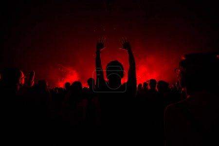 Photo for People on the concert in bright red light - Royalty Free Image