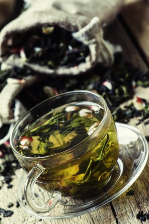 Cup of green tea with flower petals and fruits, vi...