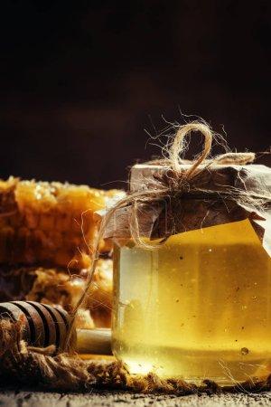Photo pour Miel de montagne dans un bocal en verre et peignes de miel, fond bois vintage, mise au point sélective - image libre de droit
