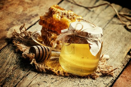 Mountain honey in a glass jar and honey combs