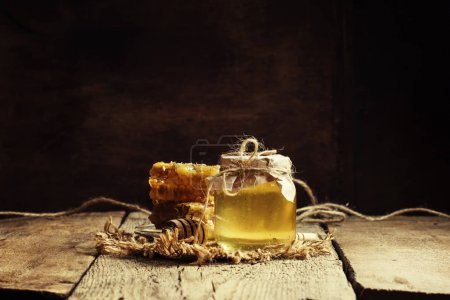 Photo for Mountain honey in a glass jar and honey combs, vintage wooden background, selective focus - Royalty Free Image