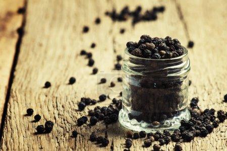 Black pepper, old wooden background