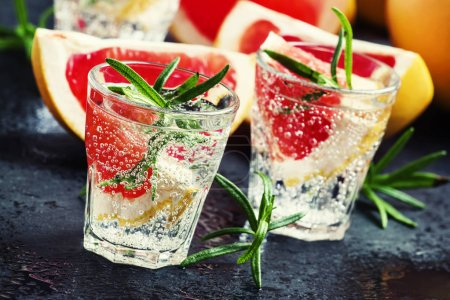 Photo pour Cocktail alcoolisé au pamplemousse, soda, glace, gin et romarin, fond de pierre sombre, mise au point sélective - image libre de droit