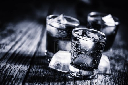 Black and white photo. Alcoholic cocktail from cola with whiskey