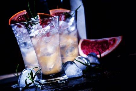 Photo pour Cocktail alcoolisé avec jus de pamplemousse, glace concassée, vodka et romarin, lumière au néon nocturne, fond de pierre noire, mise au point sélective - image libre de droit