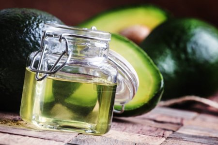 Avocado oil, old wooden background