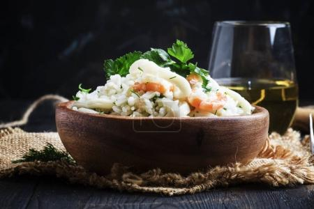 Risotto with shrimp and squid in a wooden bowl