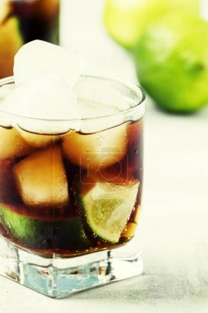 Alcohol cocktail with lime, ice and cola