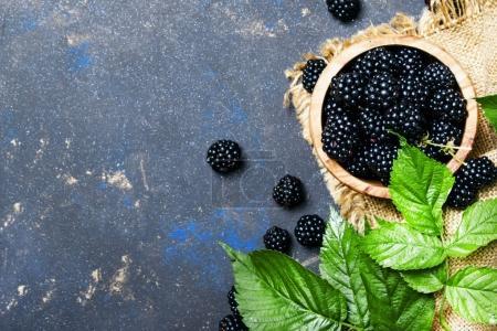 Photo pour Mûres fraîches avec des feuilles vertes dans un bol, le fond de nourriture, la vue de dessus - image libre de droit