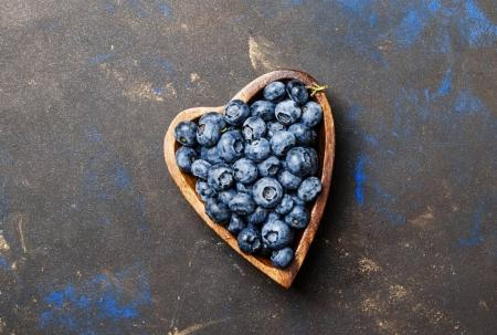 Fresh blueberries in a bowl in the shape of a heart