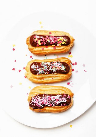 Eclairs cakes with chocolate icing and colorful sugar powder