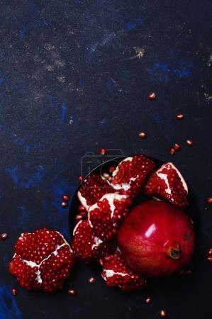 Red Pomegranate On The Plate, Black Background, Top View