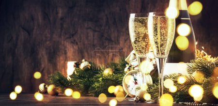 Photo for Two champagne glasses and christmas decoration on wooden snow golden bokeh background. Happy New Year Celebration. Selective focus and small depth of field - Royalty Free Image