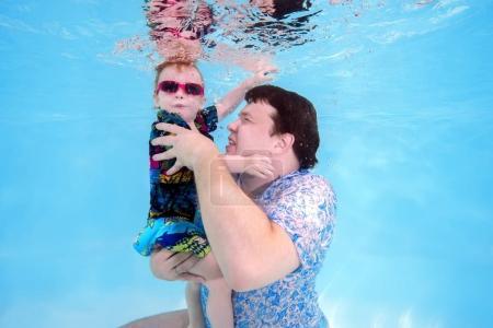 Photo pour Papa et fils jouant sous l'eau dans la piscine - image libre de droit