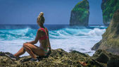 Girl sitting on the Rock and watching Huge Waves hitting Tembeling Coastline at Nusa Penida Island, Bali Indonesia