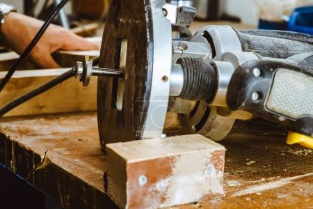 Processing of a furniture part by a machine for polishing a tree. the grinding machine on a board, selective focus.