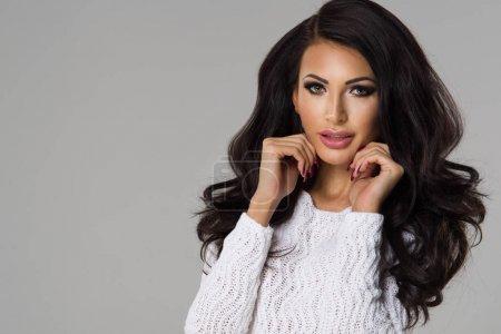 Photo pour Femme brune sensuelle avec de longs cheveux bouclés en pull blanc - image libre de droit