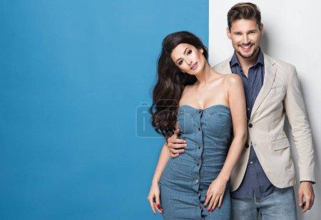 Photo pour Portrait de mode de jeune couple en vêtements décontractés étreignant sur fond studio blanc-bleu - image libre de droit