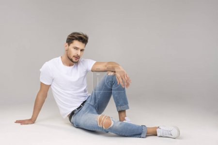 man in jeans sitting on floor