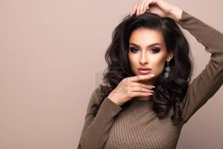 Sensual beautiful brunette woman over grey background