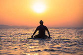 Silhouette of man sitting on surfboard at sunset over sea