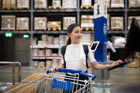 Photo pour Une femme utilise un chariot pour acheter des meubles dans un entrepôt - image libre de droit