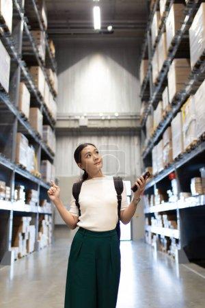 Photo pour Femme magasinant des meubles en entrepôt et utilisant un téléphone intelligent pour vérifier le prix - image libre de droit