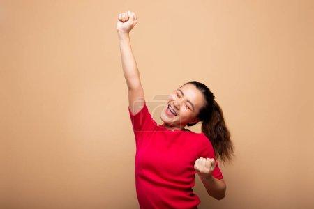 Photo pour Femme heureuse faire geste gagnant isolé sur fond - image libre de droit