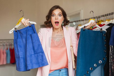 Emotional attractive woman holding apparel on hang...