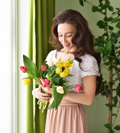 Beautiful young woman with tulip bouquet