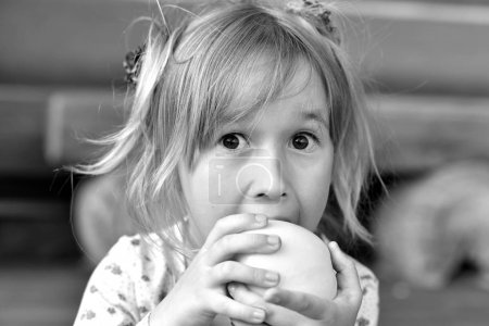 Photo for Little girl eating an apple  on background - Royalty Free Image